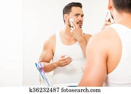 Man putting shaving cream on his face