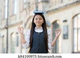 Calm the mind. Little child do meditation outdoors. Small girl do mudra hands holding book on head. Meditation for mental balance. Meditation course for beginner. School and education. Best therapy