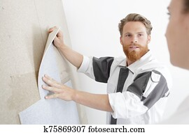 a handyman is fixing wallpaper