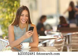 Girl texting on the phone in a restaurant