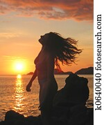 A woman in profile moving her head on her long hair at the sunset, Labuan Bajo, Pede Beach, Flores island, Indonesia