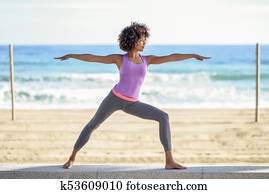 Black woman, afro hairstyle, doing yoga in warrior asana in the beach