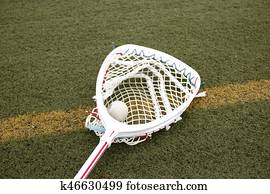 Goalies lacross stick with a ball in the net