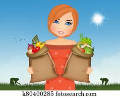 woman collects vegetables in the vegetable garden