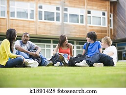 College students sitting and talking on campus lawn
