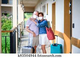 Senior couple with face masks and luggage outside apartment on holiday.