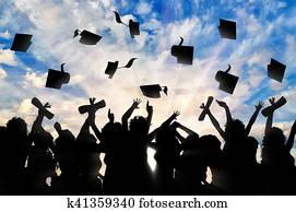 Students graduate cap throwing in sky