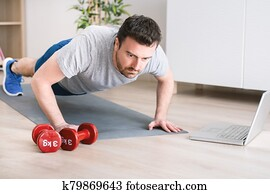 Man doing exercise while watching tutorial on laptop at home
