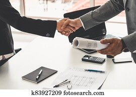 Businessman handshake businesswoman in office.