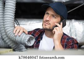young repairman contractor repairing heating panel