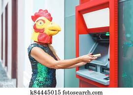 Mature woman wearing cock mask withdraw money from bank cash machine with debit card - Surreal image of half human and animal - Absurd and crazy concept of ATM advertise