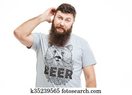 Confused thoughtful bearded man scratching his head