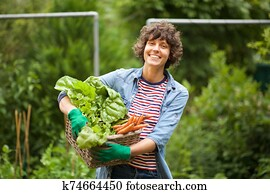 female farmer smiling with bunch of vegetables in basket