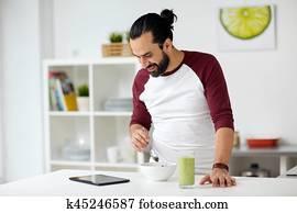 Homme avec tablet pc prenant son petit déjeuner à la maison