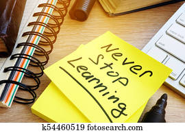 Never stop learning written on a memo stick. Lifelong learning concept.