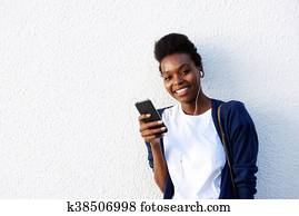 Stylish Young African American Woman Leaning Against Wall