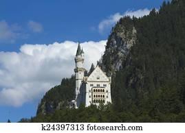 Neuschwanstein Castle amongst green trees, Bavarian Alps.