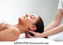 Physiotherapist pressing back of womans head.