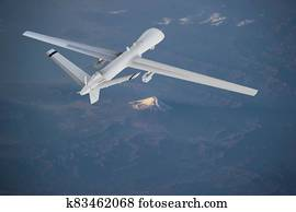 unmanned RC military drone flies over mountains at sunrise. Elements of this image furnished by NASA