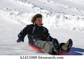 Boy Sledding Fast Down the Hill on a Red Sled