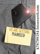 Writing note showing We Are Getting Married. Business photo showcasing Engagement Wedding preparation Loving couple Small wallet inside trouser front pocket near notation paper.