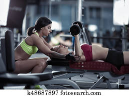 Female personal trainer helping