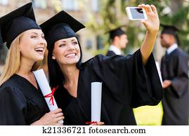 Capturing happy moments. Two happy women in graduation gowns making selfie and smiling while two men standing in the background
