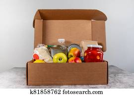 Open donation box food supplies for people in isolation on gray table
