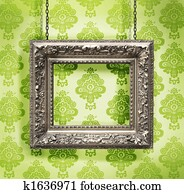 Silver picture frame hung against floral wallpaper background