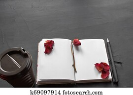 Top view of an empty notebook, scrapbook accessories and a cup of coffee on a black background.