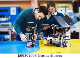 Young students of robotics working on project
