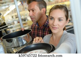 shoppers choosing pans in professional wholesale store