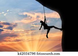 Mountaineer climbs cliff sunset