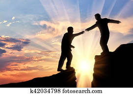 Man helps friend in mountains of giving helping hand sunset
