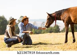 cowboy and cowgirl playing with foal