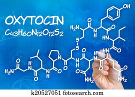 Hand with pen drawing the chemical formula of Oxytocin
