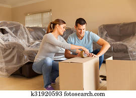 couple sealing moving boxes