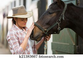 cowgirl talking to a horse