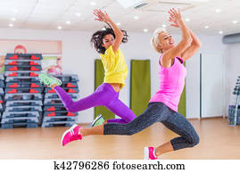 Two fitness models exercising in gym, dancing Zumba.