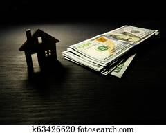 Model of home and money in the dark. Mortgage or dollars for rent concept.