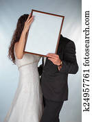 Bride and groom with a frame for photos