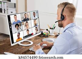 Businessman Video Conferencing With Team On Computer