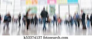 defocused business people walking in trade show hall