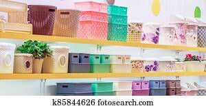 A lot of plastic household goods for home and everyday life, colorful products on the shelf of a store window, containers, buckets, storage baskets, basins