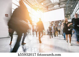 anonymous blurred people at a trade show, including copy space banner