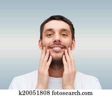 beautiful smiling man touching his face