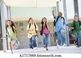 Six students running away from front door of school excited