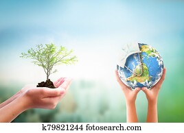 Earth Day concept: hands holding Corona virus or COVID-19 Earth globe wearing a mask and tree over nature background. Elements of this image furnished by NASA