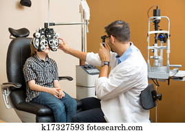 Optometrist Examining Preadolescent Boy's Eyes