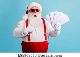 Portrait of his he nice attractive amazed stunned thick white-haired Santa holding in hand demonstrating mail gifts wish list omg isolated bright vivid shine vibrant blue color background